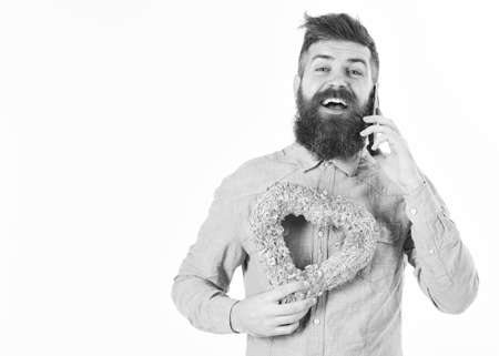 Macho with beard and romantic gift. Hipster smiles with pink heart and happy face. Bearded man holds gift and talks by phone. Dating, Valentines day, greeting, surprise concept. Brutal man in love