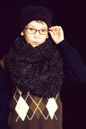 small serious boy or cute nerd kid in glasses, hat and fashionable knitted scarf on black backgroun