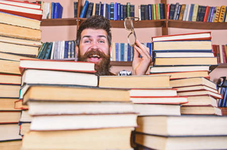 Man on happy face between piles of books in library, bookshelves on background. Teacher or student with beard wears eyeglasses, sits at table with books, defocused. Scientific research concept