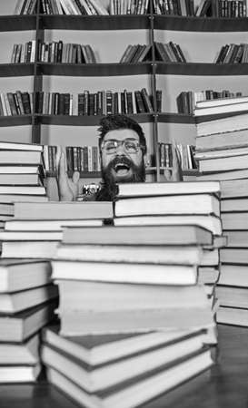 Scientific discovery concept. Man on excited face between piles of books in library, bookshelves on background. Teacher or student with beard wears eyeglasses, sits at table with books, defocused