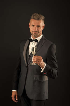 Cheers. Sincere greetings. Appreciate classics. Bearded man with formal look. Hipster black background. Brutal man in tuxedo suit. Classic can make man look smarter. Celebrate with champagne glass