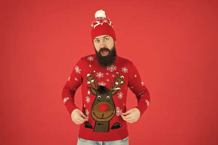 eve of St Nicholas. surprised hipster red background. lets go shopping. time for choosing a gift. should i wear warm clothes. bearded man in knitted accessory. its christmas time. happy new year