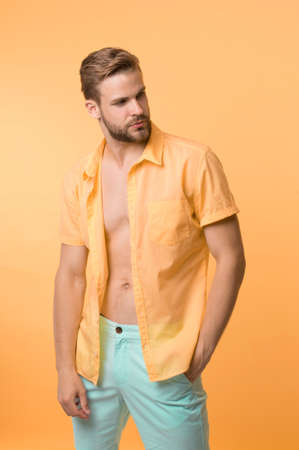 Man calm face posing confidently yellow background. Guy wear unbuttoned shirt with smooth skin on chest. Hair removal procedure. Take off clothes and not be ashamed. Male hair depilation chest