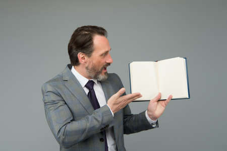 Surprised bearded man in formal business suit show open book for information, copy space