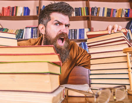 Teacher or student with beard sits at table with glasses, defocused. Man on shouting face between piles of books, while studying in library, bookshelves on background. Mad scientist concept Reklamní fotografie