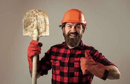 well done. engineer architect in safety helmet. brutal technician builder. factory worker mechanic. industrial worker in helmet. man hold shovel in gloves. construction worker in hard hat