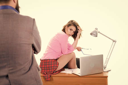 Lets repeat the previous lesson. Pretty tutor teaching business lesson to businessman. Man looking at sexy school teacher sitting on desk. Sensual woman giving online lesson. Business school lesson