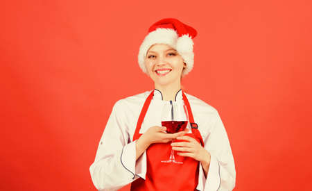 Enjoy easy ideas for holiday parties and holiday dinners. Festive menu concept. Christmas dinner ideas. Christmas menu. No stress. Woman chef cooking wear santa hat drink wine. Best christmas recipes Standard-Bild