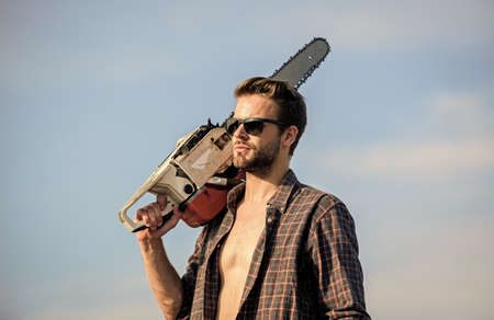 Gardener lumberjack equipment. Get stylish haircut. Barbershop concept. Masculinity concept. Handsome man with chainsaw blue sky background. Dangerous job. Powerful chainsaw. Lumberjack hold chainsaw