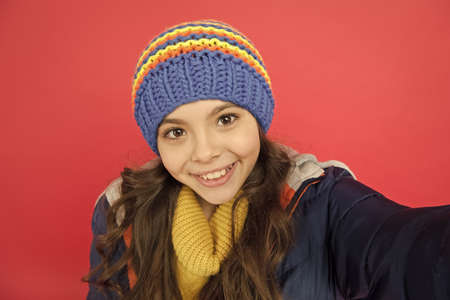 Selfie camera. Smiling cute face. Little girl wear winter clothes red background. Childhood concept. Emotional girl long hair knitted hat. Teen girl casual style. Emotions and mood. Personal blog