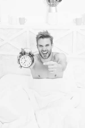 Look at this clock. Stressful man point finger at clock face. Sexy guy slept through alarm clock. Lack of time. Being late. Morning routine. Nightmare. Ghastly dreams. Waking up. Awakening