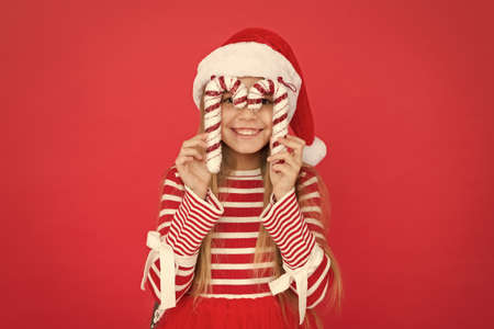 santa elf kid candy cane decor. xmas holiday decoration. christmas shopping time. happy new year celebration. festive party in red color. sweet childhood happiness. small girl having fun