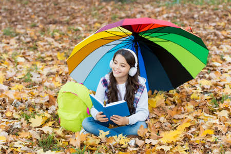fall leaves in park. back to school. online education. seasonal weather. happy kid wear headphones under umbrella. girl listen music and read book. child relax in autumn forest. Is it raining