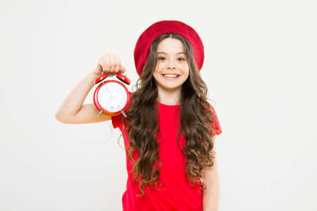 little girl in french style hat. beauty hairdresser and fashion. child with alarm clock. Timeless fashion. parisian child. happy girl with long curly hair in beret. fashion is fleeting. fashion time 스톡 콘텐츠