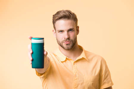 Man on confident face recommends shampoo, yellow background. Guy with bristle holds bottle of shampoo, copy space. Man reaches hand out to show bottle of shampoo. Hair care and shampoo concept