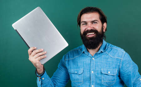 elearning the subject. back to school. happy teachers day. brutal man with beard hold computer. informal education technology. male student sit in classroom while lesson. pass the exam