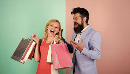 Consumerism addictive behavior. Couple in mall. Shopaholic girlfriend. Black friday concept. Woman on shopping tour. Man girl with paper bags. Addicted shopaholic. Shopaholic problem. Spending money