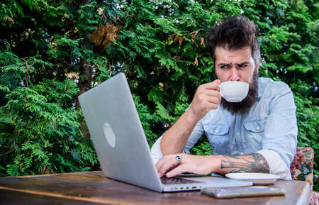 Visiting Internet cafe. Hipster enjoying tea and free wifi in outdoor cafe. Bearded man drinking and browsing the Web in cafe. Cyber cafe providing Internet access and freshly brewed coffee