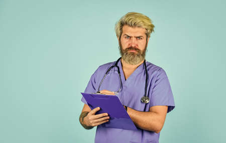 he is wearing a stethoscope. nurse holding binder and wearing stethoscope. mature bearded male doctor with a folder in uniform standing. Portrait of serious nurse with a folder