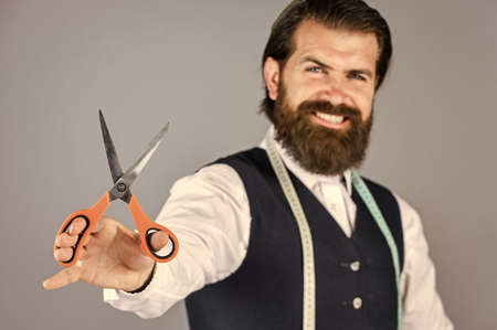 successful sartor ready to work. formal and office style. man tailor with tape measure and scissors. man tailoring male clothes. brutal man is fashion designer. man designing for men. selective focus Standard-Bild