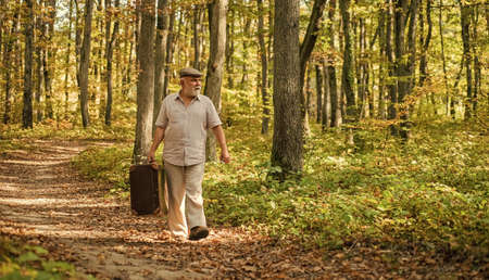 Traveling and vacation. Fall season. Idyllic nature. Old man walk with suitcase. retirement concept. Old man carry travel bag in woodland. senior person travel through autumn forest. Pleasure travel