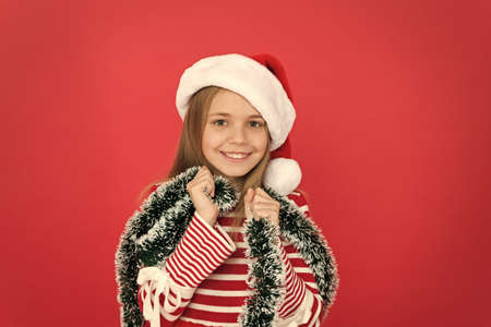 funny little id play with tinsel. santa kid with tinsel decor. xmas holiday decoration. time for christmas shopping. happy new year. festive party in red color. happy childhood. small girl having fun.