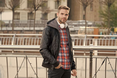 Modern lifestyle and technology. Handsome man wear headphones outdoors. Caucasian guy in casual street style. New technology. Music technology. Urbanization and urban life
