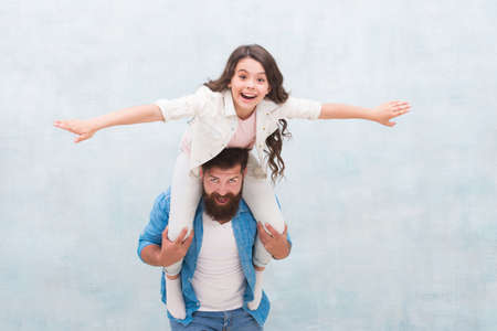 Flight of imagination. Father ride daughter child pretending flying. Happy family have fun together. Playing airplane. Childhood imagination. I believe I can fly