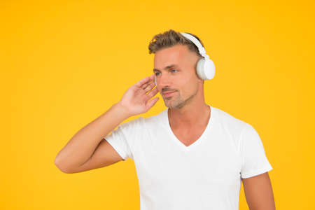 Serious middle-aged caucasian man listen to music playing in modern headphones in casual style yellow background, sound, copy space