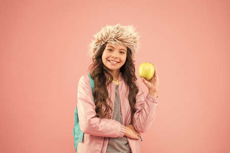 end of winter semester. holiday and vacation. kid pink backdrop. teen daily life. education and happy people schoolgirl with books after lesson. school break. small happy girl earflap hat eat apple