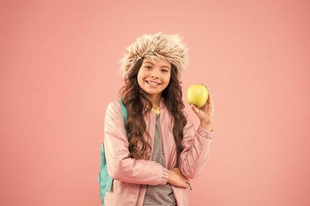 冬季学期结束。假期和假期。孩子粉红色背景。青少年日常生活。教育和愉快的人女小学生有书的课程。学校放假。小快乐的女孩耳环帽子吃苹果