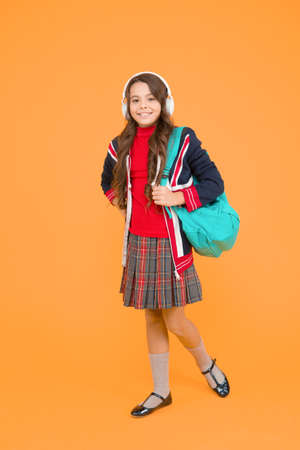 small girl headset with backpack. kid with english flag on jacket. study english language online. Improve your English with audio lessons. vacation in great britain. ebook and private lesson concept