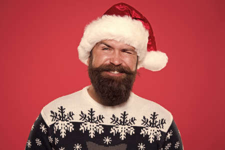 christmas time. smiling bearded man santa hat. brutal hipster favorite sweater red background. winter holiday fun. happy face mustache. portrait of santa man with beard. new year party. Jingle bells