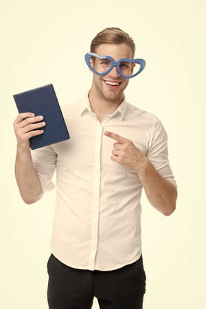 I choose book. Happy man point finger at book. Funny guy read book in fancy glasses. Nerd and bibliophile. Geek and bookworm. Home library. Book shop. Reading makes you smart