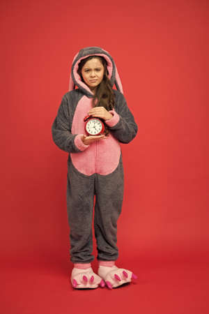 little girl wear easter bunny costume. Early rise. sad kid in kigurumi pajama hold alarm clock. time to wake up. sweet dreams. good morning to you. people and bedtime concept Standard-Bild