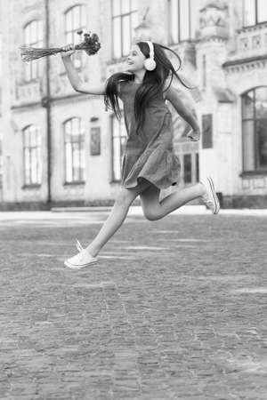 Happy girl in energetic jump outdoors. Energetic mood. Fresh vibes. Music and entertainment. Summer vacation and holidays. Leisure and free time. Energetic and unstoppable