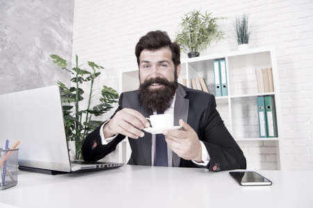 Discuss business over coffee. Man handsome boss sit in office drinking coffee. Comfy workspace. Bearded businessman formal suit relaxing with coffee. Office life routines. Really good cappuccino