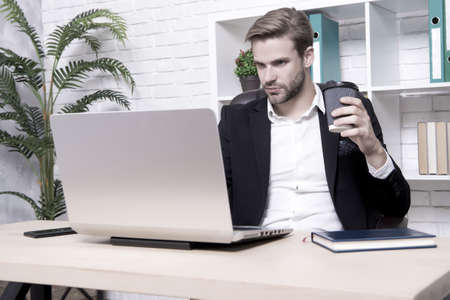 Handsome man in business office. Inspired with cup of fresh coffee. Starting own business. Ceo head office concept. Business development. Businessman drinking coffee. Confident man use laptop