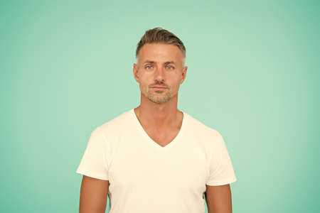 Man abstract blue background. Caucasian middle age man. Handsome man in casual style. Fashion and style. Unshaven man with beard hair. Barbershop. Hair salon