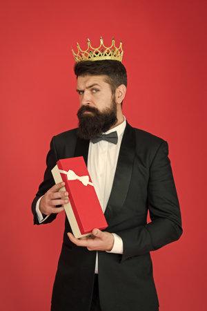 Being complete egoist. Egoist hold present box red background. Bearded man wear crown. Egoist or big boss. Egoist and selfish. Egoism and vanity. Pride and haughtiness. Holiday celebration Foto de archivo