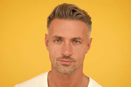 Skincare is essential. Handsome man yellow background. Caucasian guy with normal skin and facial stubble. Skin health. Skincare products. Skincare routine and grooming. Skincare for middle age men