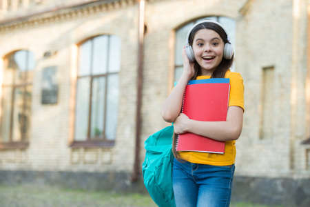 Learn naturally, speak naturally. Happy kid wear headphones outdoors. English school. Foreign language courses. Audio lesson. Modern education. Technology for language learning, copy space