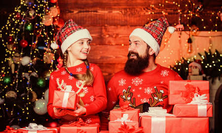 Father bearded man and daughter near christmas tree. Spend time with family. Dad and child opening christmas gifts. All this is from santa. Happy holidays. Favorite childhood memories of christmas Stock Photo