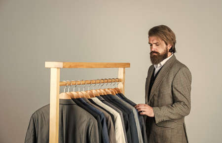 Turning ideas into clothing. Man in custom tailored suit presenting expensive tailored tuxedo. Man clothing in boutique. Man with suit. tailor in his workshop