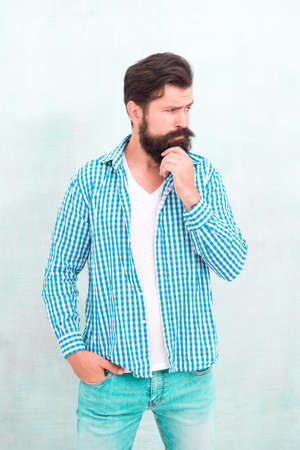 Attractiveness concept. Well groomed guy. Brutal handsome hipster man grey wall background. Bearded man trendy hipster style. Masculinity and male beauty. Hipster with beard and mustache wear shirt