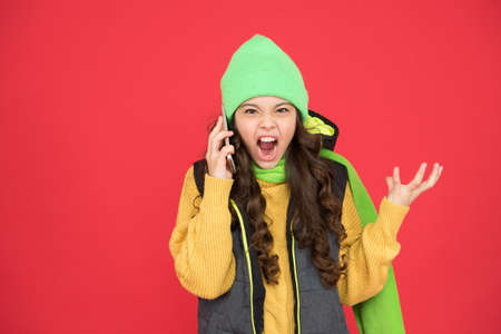 angry teen girl in warm winter clothing speak on phone on christmas holidays, bad news
