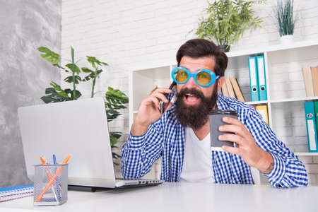 Happy bearded man in cool glasses drink coffee talking on mobile phone in modern office, addiction