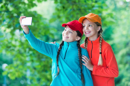 Happy girls with beauty look pose for selfie camera phone on natural landscape, self-portrait photograph