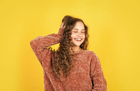 little beauty with stylish look. small girl with long curly hair. fashion model kid has brunette hairstyle. hairdresser for child. shampoo cosmetic for hair. happy childrens day. Young and free