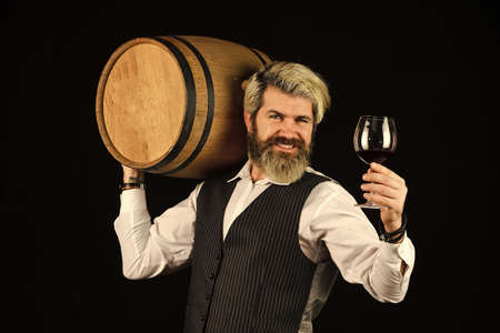 I recommend this. Bartender at wine cellar with exquisite drink. experienced sommelier taste wine. barman tasting red wine at degustation. male sommelier appreciating drink. barrel of red wine